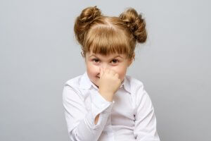 Child Holding Her Nose From Smelling Bad Breath