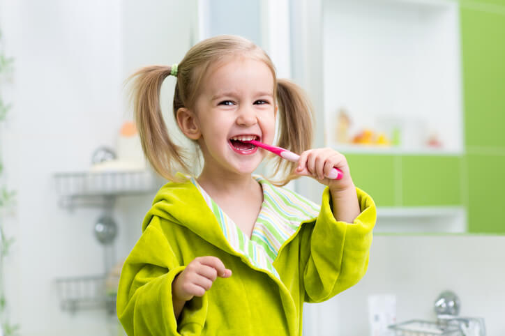 smiling little girl brushing teeth