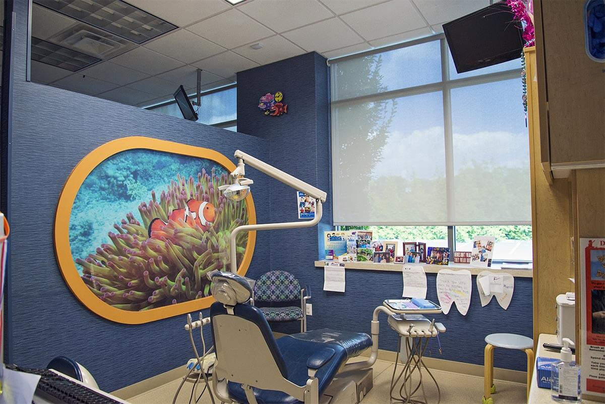 dental exam room with blue chair and underwater image on wall