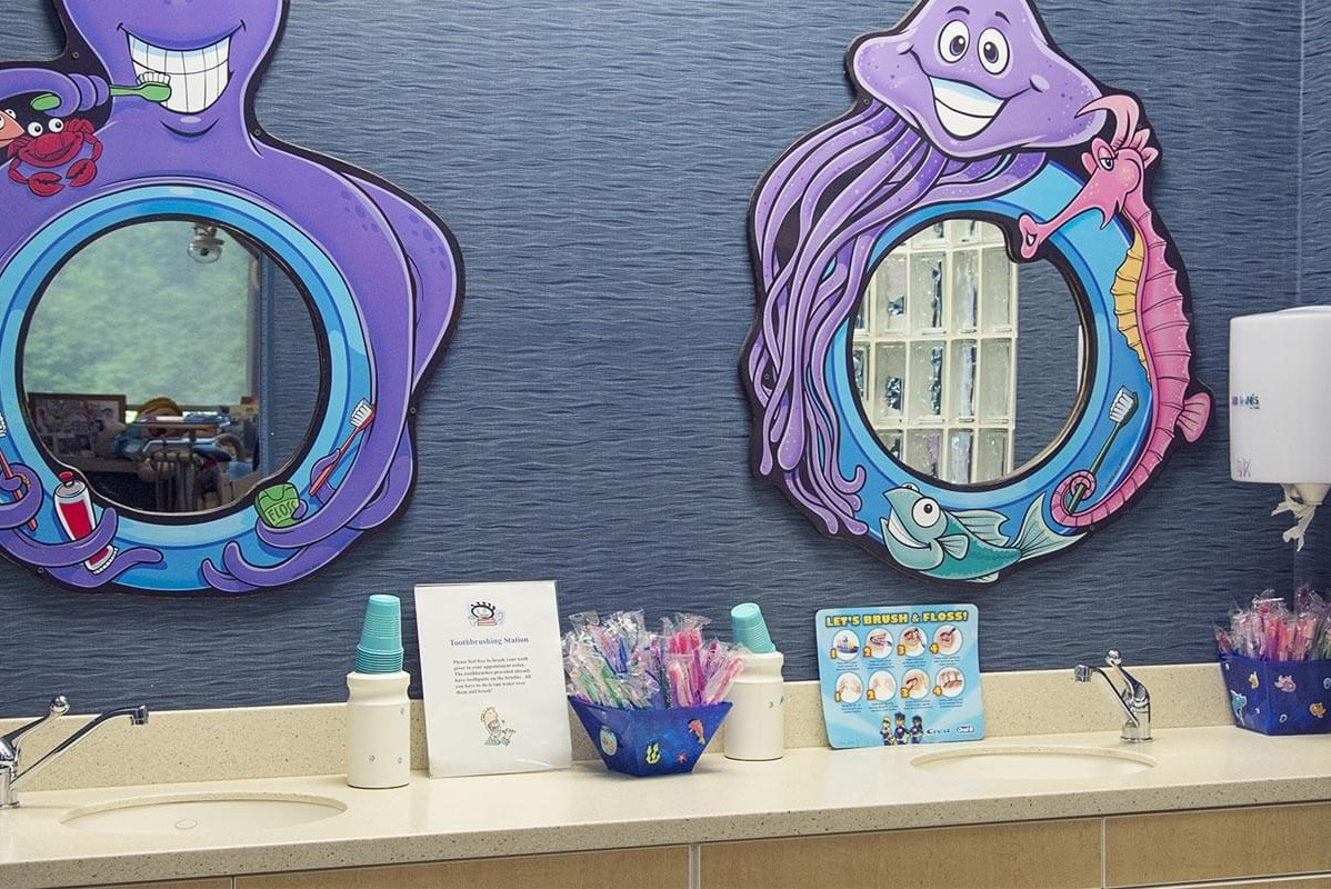 brushing station in dental office with two sinks and mirrors