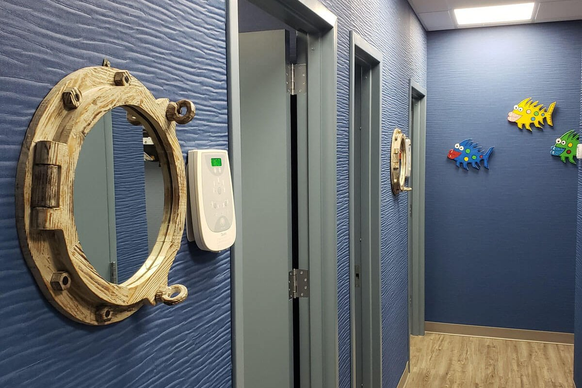 nautical themed hallway with blue walls and grey doors