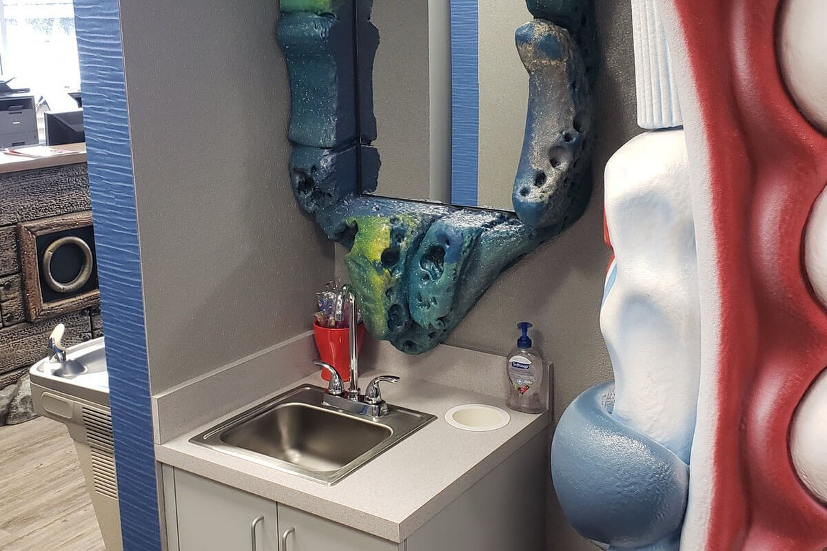brushing station with a sink and mirror