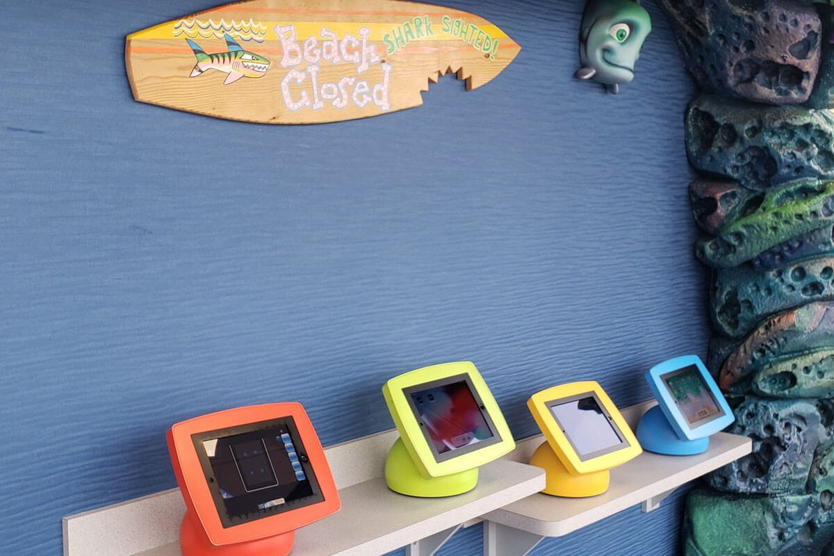 dental waiting area with four tablets for kids