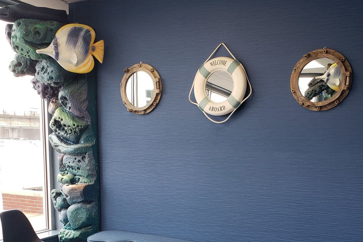 port windows and life preserver mirrors on blue wall